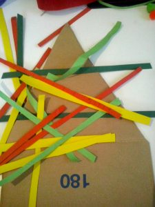 ....tagliate una sagoma a forma di triangolo...e tante strisce di carta colorata o di vecchi giornali...